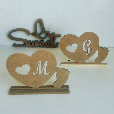 MDF structure in the shape of a heart with little feet and the first letter of the baby's name