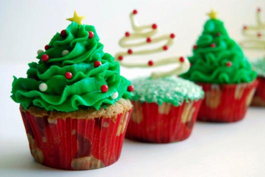 Christmas cupcake decorated with whipped cream tree and red confetti.