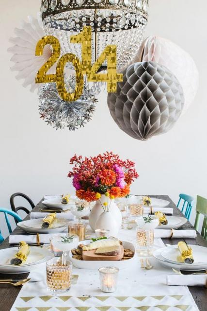 Table decorated with white items and hanging balloons.