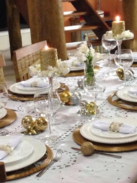 Decorated table for New Year's dinner, with candles and flowers.