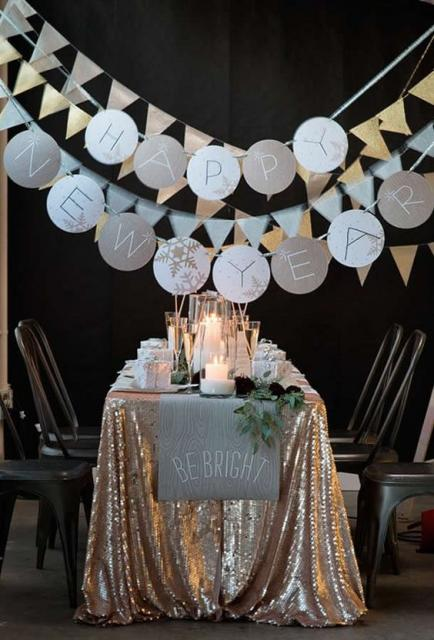 Table decorated with golden tablecloth and little flags hanging from the top.