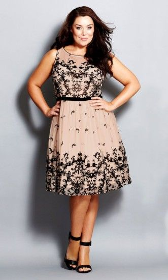 Model wears plus size party dress in nude color with black lace details and black sandals.