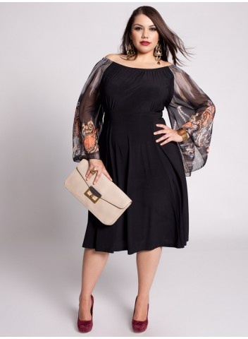 Model wears black dress with transparencies and nude bag.