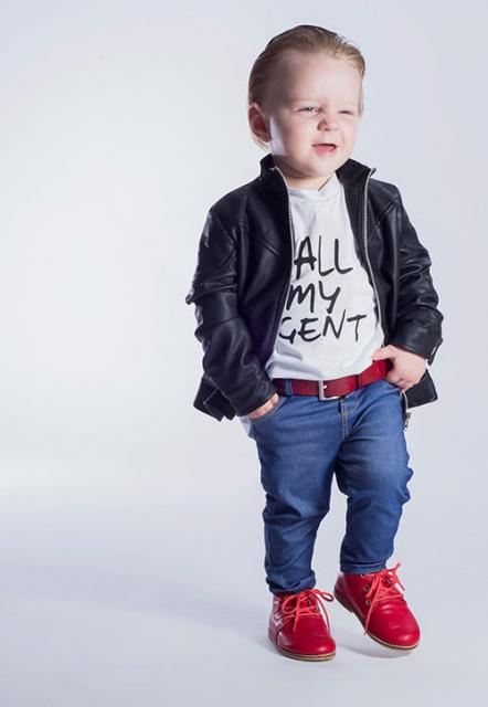 Boy in jeans, red belt, white t-shirt and black jacket.