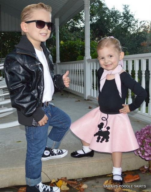 Boy in jeans, black jacket and sunglasses and girl in pink skirt, black blouse, white sock and black shoes.