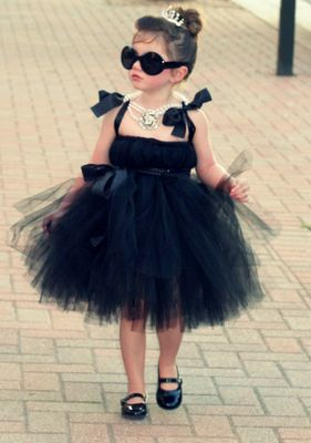 Girl in black dress, sunglasses and pearls, imitating Audrey Hepburn, from the movie Baby Doll.