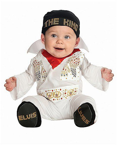 Baby in white overalls and gold details.