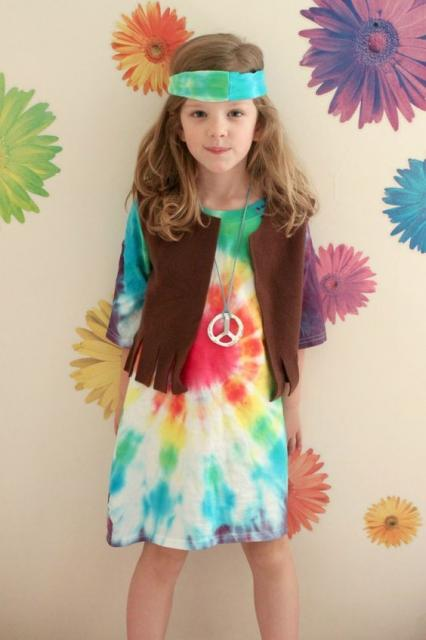 Girl in colorful dress, brown vest and headband.