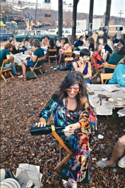 Janis Joplin at a festival, wearing a dress and colorful glasses.