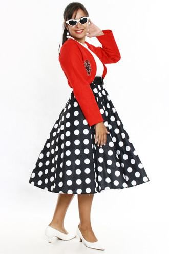 Woman in black skirt with white polka dots, white t-shirt and red jacket.