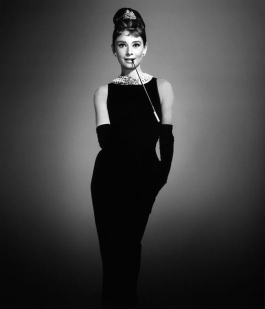 Audrey Hepburn in black dress and gloves.