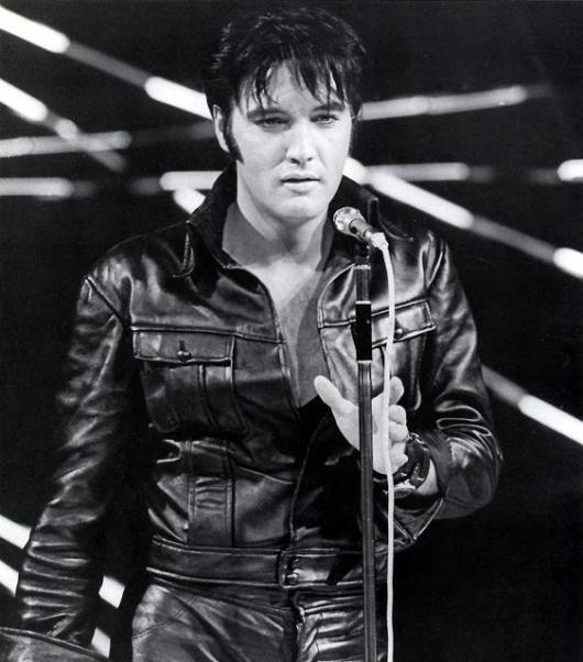 Elvis Presley singing in a leather jacket.