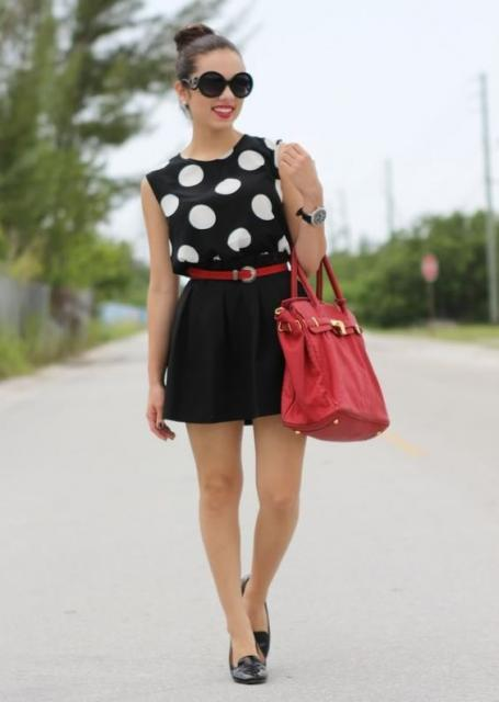 Woman in black skirt and black blouse with white polka dots.