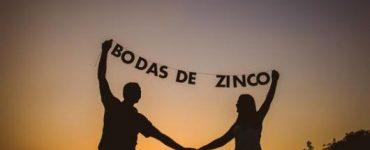 "Couple holding letters that form the sentence "" zinc wedding""."